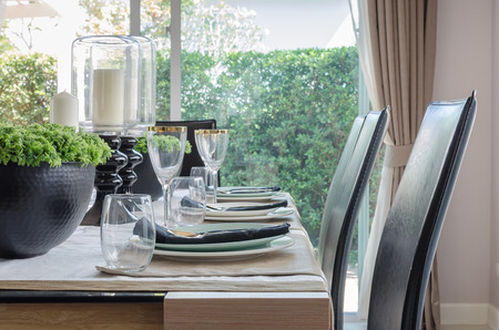 dinning table: table set for dinner on dinning table with black modern chair at home