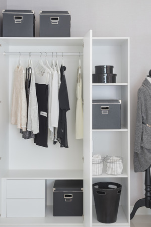 black and white clothes hanging in white wardrobe Stockfoto
