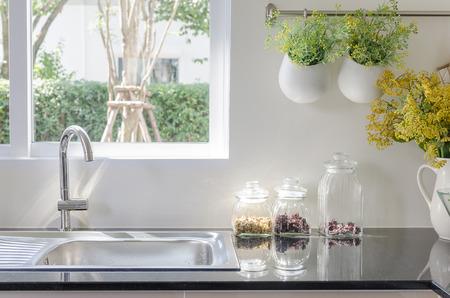 cucina moderna: lavello moderna sul contatore di cucina nero con un vaso di piante Archivio Fotografico