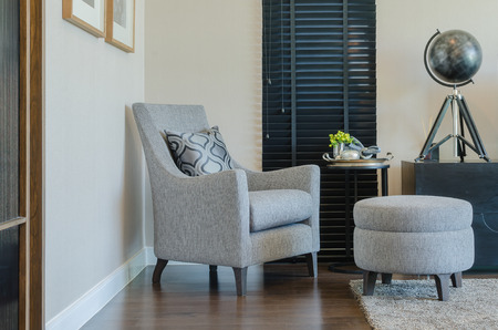 classic living room: classic style chair and round bench with black curtain in living room