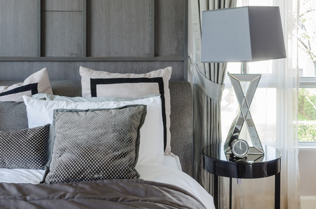 modern bedroom design in black and white color scheme with modern lamp on side table Archivio Fotografico