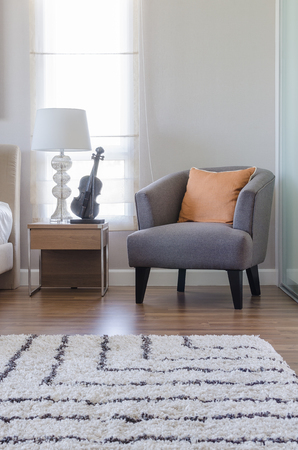orange pillow on modern grey chair with bedside table and white lamp in bedroom at home
