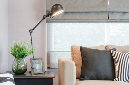 lamp: modern living room with black lamp on table side and glass vase of plant