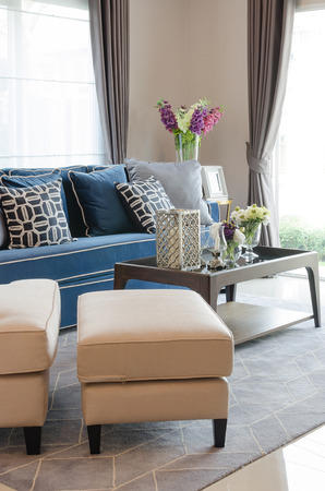 classic living room: luxury living room with blue classic sofa and pillows, wooden table on carpet at home