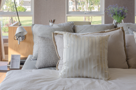 bed linen: modern bedroom with wooden bed and pillows at home