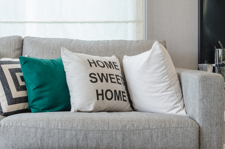 sofa: modern grey sofa with black and white and green pillows in living room