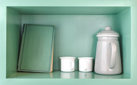 shelve: old green book, white tea cup and grey jug in green wooden shelve