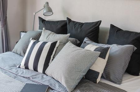 cama: dormitorio moderno con almohadas de tono de color oscuro en la cama