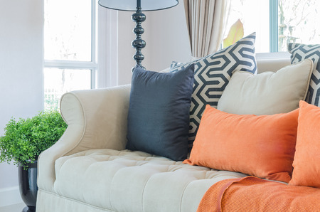pillow: orange pillows and blanket on modern sofa in living room at home