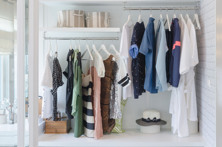 clothes hanging in closet with hat at home Stockfoto