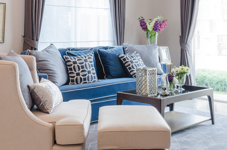 classic blue sofa with pillows and wooden table on carpet in living room at home