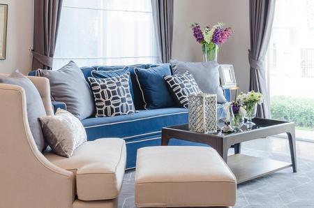 Classico divano blu con cuscini e tavolo di legno sul tappeto in salotto a casa Archivio Fotografico - 45738582