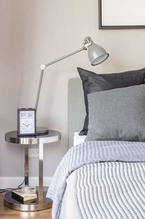 side table: modern grey lamp with alarm clock on side table in bedroom at home Stock Photo