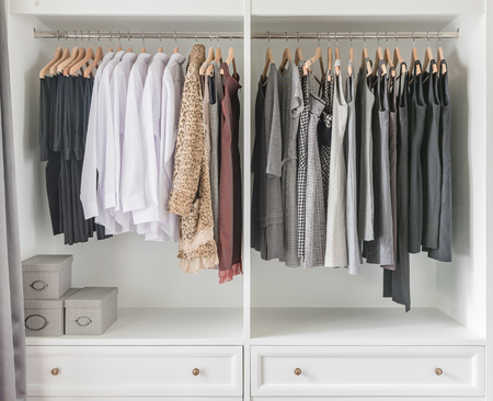 white wardrobe with clothes hanging on rail