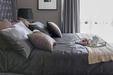 Letto di lusso con cuscini e vassoio con tè impostato sulla coperta in camera da letto Archivio Fotografico - 47364919