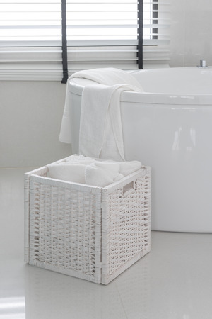 in the basket: white towel in wooden basket with modern bath tub in bathroom Stock Photo