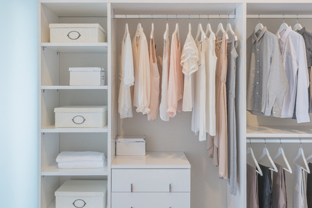 clothes hanging on rail in white wardrobe with boxes