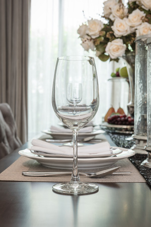 dinning room: empty wine glass on wooden dinning table with table set in dinning room Stock Photo