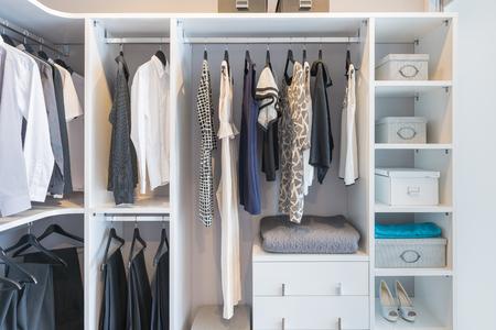 tela algodon: ropa colgada en el carril en el armario blanco con caja y zapatos Foto de archivo
