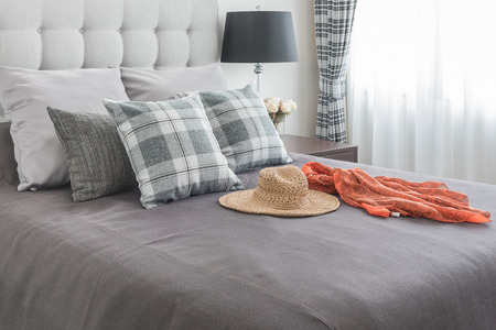klasyczne łóżko z poduszkami, kapelusz, tkaniny i czarne lampy w sypialni