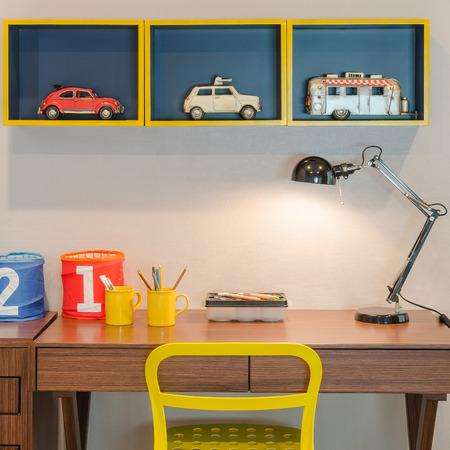 psací stůl: žlutá židle a dřevěný stůl s moderním černým lampou v dětském pokoji