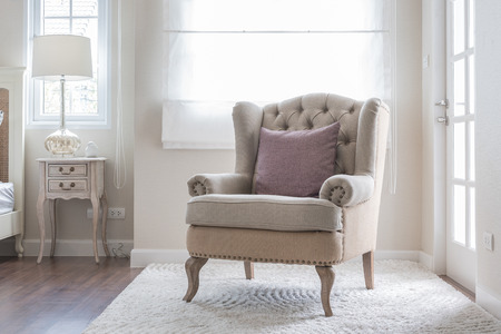 classic chair on carpet with pillow in bedroom