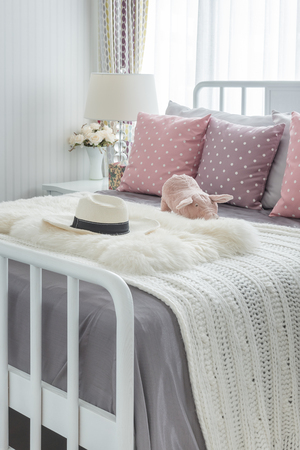 bedroom suite: pink pillows with pink doll on white wooden bed and classic hat in bedroom