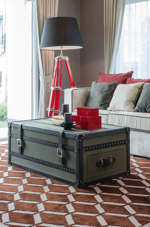 furniture design: black lamp and sofa with casket as table on brown carpet in luxury living room