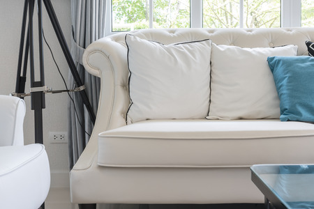 white sofa: luxury living room with white pillows on classic style sofa at home Stock Photo