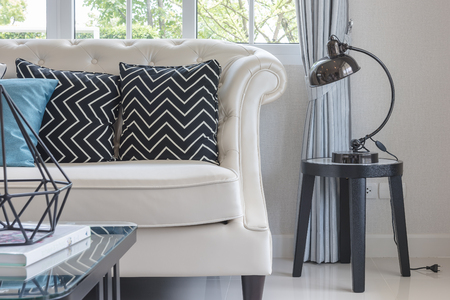 luxury living room with pillows on classic style sofa and lamp on table side Banque d'images