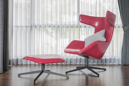 modern chair: Modern red chair on wooden floor with curtain as background Stock Photo