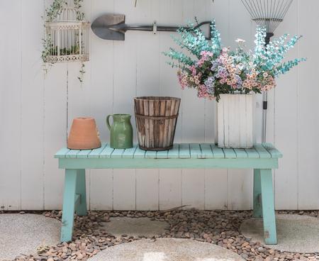 花の庭で白い木製パネルの壁と緑のベンチに