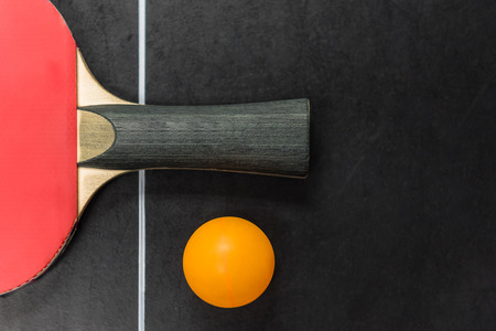 table tennis racket with ball on black table, top view Standard-Bild
