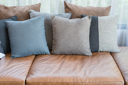 brown leather sofa: pillows on brown leather sofa in modern living room