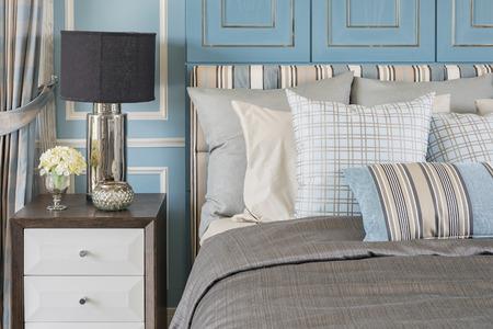 Classico stile lampada sul tavolo di legno in camera da letto blu con letto e cuscini classico Archivio Fotografico - 48533434
