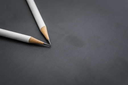 secretarial: two white pencils on black background