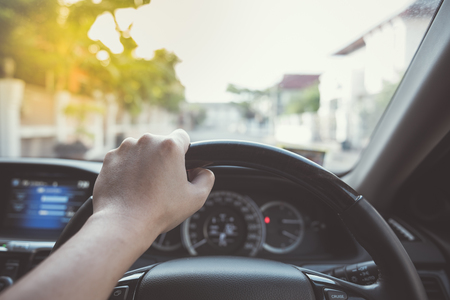 driver cap: hand of driver on steering wheel of car - vintage picture style Stock Photo