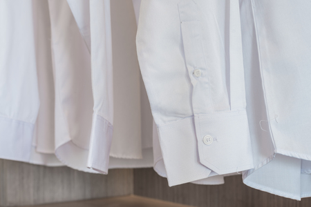 laundered: white shirts hanging on rack with white buttons