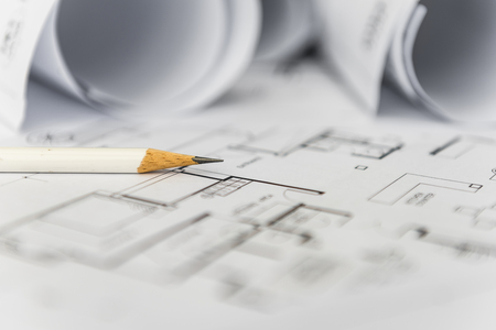 engineering tools: white pencil on architectural for construction drawings  with roll of blueprint