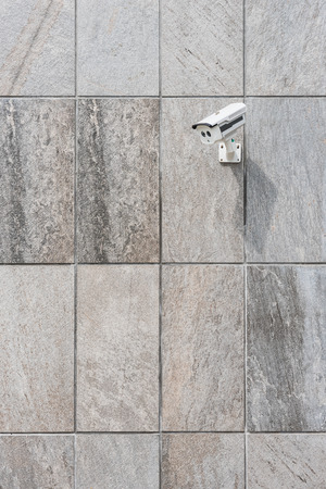 nightvision: CCTV security camera on stone wall pattern Stock Photo