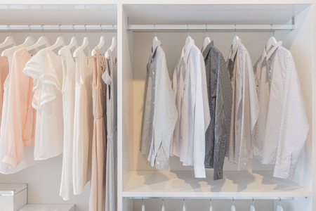 dress and shirts hanging on rail in white wardrobe