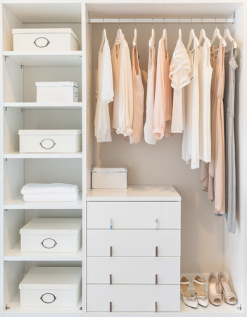 clothes closet: white wardrobe on wooden floor with dress hanging on rail