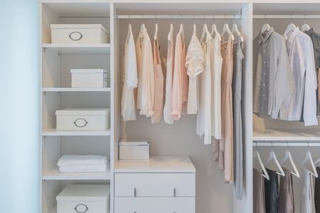 tela algodon: ropa colgada en el carril en el armario blanco con cajas Foto de archivo