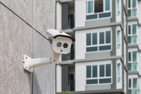 nightvision: dirty CCTV security camera on stone wall Stock Photo