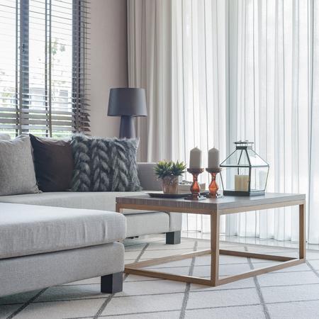 moderna sala de estar con sofá moderno y almohadas en la alfombra Foto de archivo