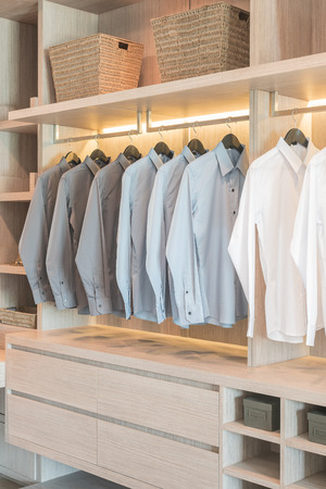 row of shirts hanging on rail in wooden wardrobe