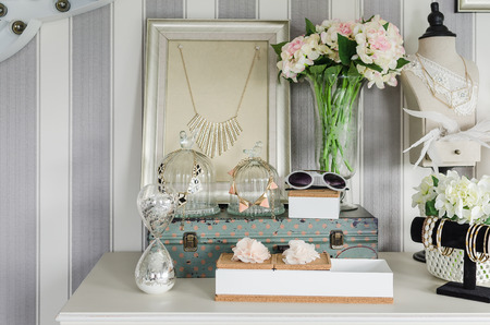 women's accesories on white dressing table at home