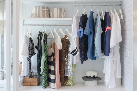clothes hanging in closet with hat at home 스톡 콘텐츠