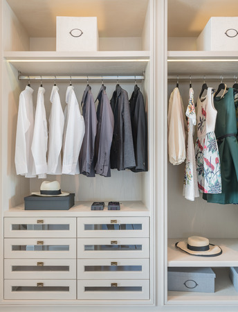 shirts and dress hanging on rail in wooden wardrobe at home