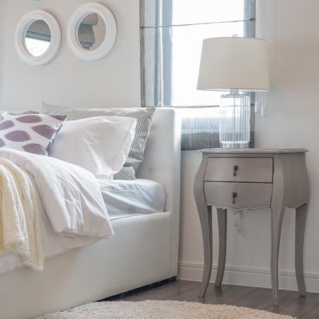 lampe blanche sur le côté de la table classique dans la chambre blanche à la maison